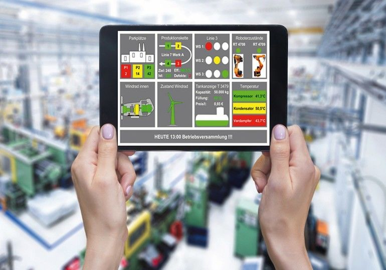 Horizontal_color_image_of_female_hands_holding_white_screen_digital_tablet_in_a_modern_plastic_production_line._Ordering_on-line_from_injection_moulding_factory_on_a_touchscreen_tablet_computer._Large_factory,_industrial_machines,_robots_and_manufacturing