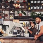 Coffee_shop_workers_standing_at_the_counter_looking_outside_the_cafe_and_smiling.
