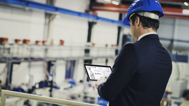 Factory_manager_supervising_the_production_process_using_a_digital_tablet.