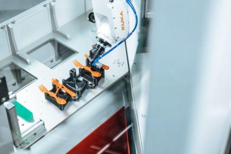 KUKA Roboter entnimmt Plastikbesteck aus Maschine.