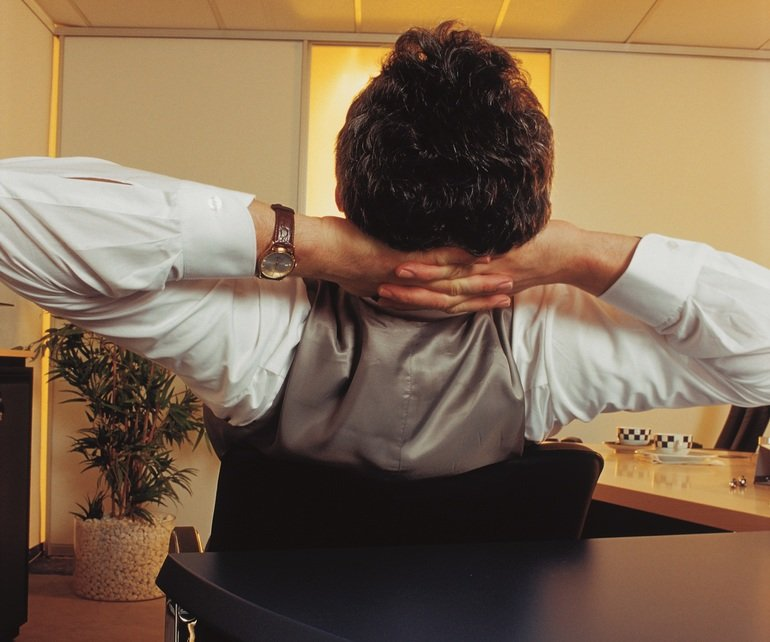 Manager_sitzt_entspannt_am_Schreibtisch,_von_hinten,_Haende_im_Nacken